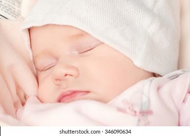 Sweet little newborn baby sleeping in her bed.