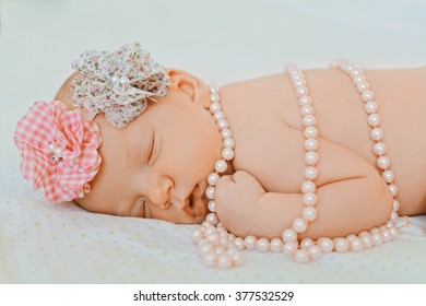 Sweet little newborn baby sleeping in her bed. A portrait of 1 month old baby girl wearing a large, pink and grey flower headband and pearls. She is lying on a soft white blanket.