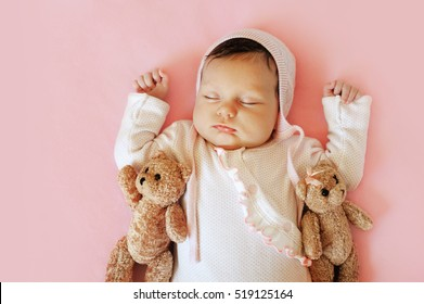 Sweet Little Newborn Baby Sleeping On The Blanket With His two bears Toy