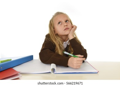 sweet little schoolgirl in school uniform sitting at studying desk doing homework looking thoughtful and absent mind in child education concept isolated on white background