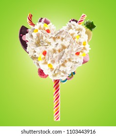 Sweet Lolipop in Heart form of whipped cream with sweets, jellies, heart front view. Crazy freakshake food trend. Front view of whipped heart of cream lolly, full of berry and jelly sweets, chocolate