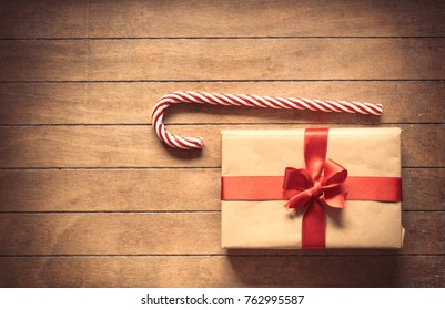 Sweet lollipop and Christmas gift box on wooden background