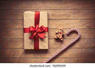Sweet lollipop with gingerbread man and Christmas gift box on wooden background