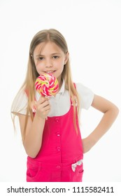 Sweet look. Little girl eat candy on stick isolated on white. Child smile with lollipop. Happy kid with swirl caramel. Food and dessert. Diet and dieting.