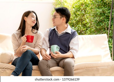 sweet and lovey asian couple husband and wife with hot drink talk together with happiness and peaceful home interior background