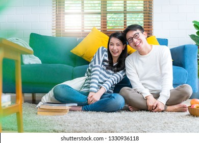 sweet lovey asian family couple sit talk good conversation on sofa in living room house background