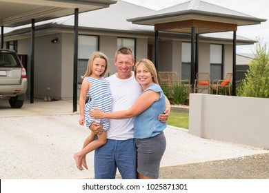 sweet loving family portrait with husband and wife holding beautiful little daughter posing together in front of modern house in happiness and lifestyle concept