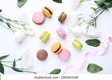 Sweet macarons with eustoma flowers on white background