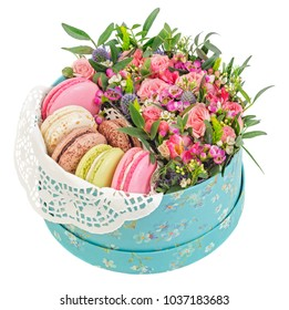 Sweet macaroons in gift box and flowers isolated on white background.