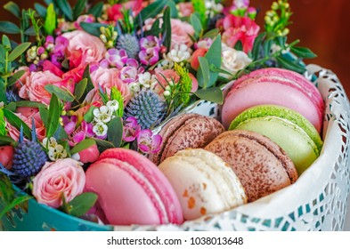 Sweet macaroons in gift box with flowers. Selective focus.