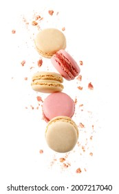 Sweet macaroons macarons with crumbs falling flying isolated on  white background. French cookies with vanilla, raspberry and strawberry. Pastry shop card