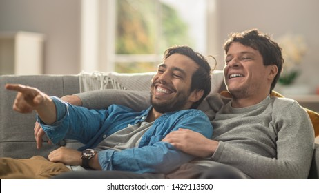 Sweet Male Queer Couple Spend Time at Home. They are Lying Down on a Sofa and Laughing. Partner's Hand is Around His Lover and Other Pointing on Screen. Room Has Modern Interior.