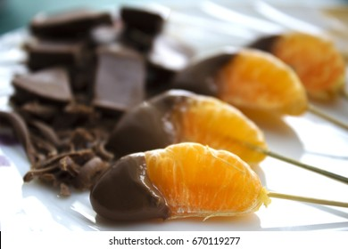 Sweet mandarin in chocolate which lies on a plate