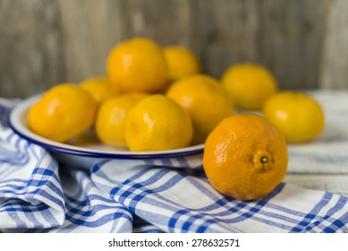 Sweet mandarin oranges on plate with tea towel in shallow depth of field