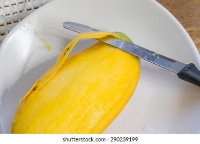 Sweet mango and knife on dish.;