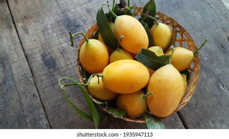 Sweet Marian plum in a bamboo basket on wooden table, concept of tropical fruits.thai fruits concept.and diet fruit.copy Space,Soft focus,Select focus