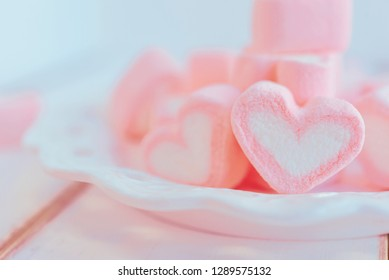 Sweet marshmallow in the shape of heart on white plate with nature background. Concept about love and relationship. Lonely feeling and waiting for someone. Valentine Day (Soft Style for Background)