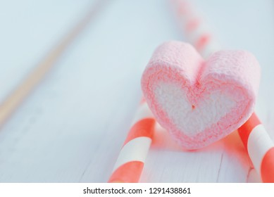 Sweet marshmallow in the shape of heart on wooden table. Decorated with pink straw. Concept about love and relationship with copy space. (Soft Style for Background)