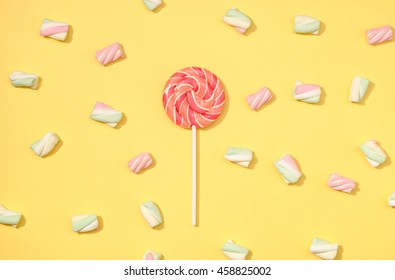 Sweet marshmallows minimalism set with red lollipop on pastel straw yellow background