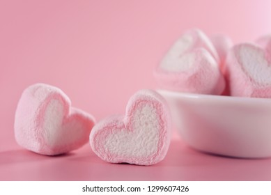 Sweet marshmallows in the shape of heart in the ceramic cup with pink background.Concept about love and relationship.Romantic and soft style for colorful greeting card.Valentine Day.