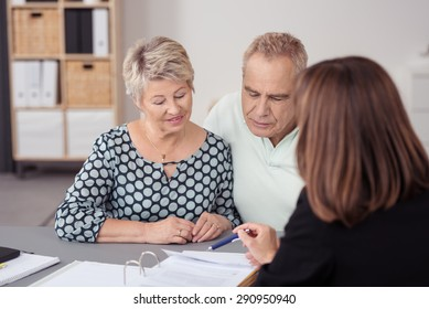Sweet Middle Aged Couple Listening to a Female Business Agent Discussing to them What is on the Document at the Table.