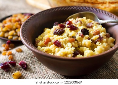 Sweet millet porridge with raisins and dried cranberries in ceramic rustic bowl