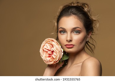 sweet model girl with pink flower rose looking in camera . she posing on beige bakground . beauty spring concept.