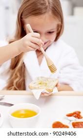 Sweet morning - little girl preparing to eat honey on bread, focus on the hand