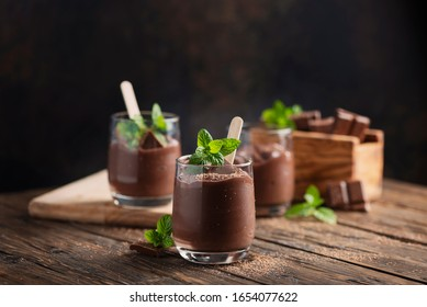 Sweet mousse with chocolate and mint on the rustic table, selective focus