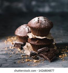 Sweet muffins with on dark textured background.