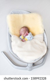 Sweet newborn baby boy sleeping in a swing on a sheepskin under a warm knitted blanket