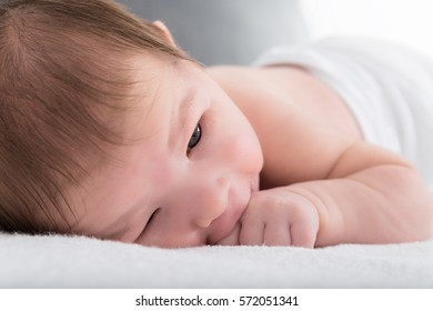 Sweet newborn baby resting on warm white blanket leaning on hand sucking thumb, Cute baby lying down on soft blanket in bedroom wearing diapers , Happy and healthy childhood with daydreaming concept