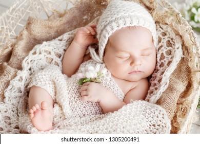 f271f5a94c9 Sweet newborn baby sleeps in a basket. Beautiful newborn boy with flowers