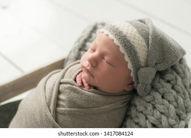Sweet newborn baby sleeps in a basket. Beautiful newborn boy in a grey knitted hat