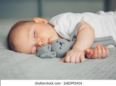 Süßes Neugeborenes schläft mit grauem Spielzeughaar