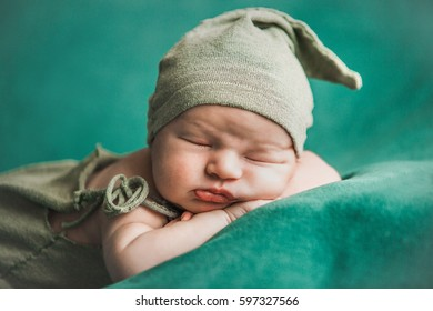 sweet newborn baby sleeps on a green blanket
