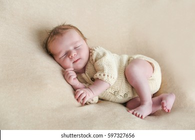sweet newborn baby sleeps on a light blanket
