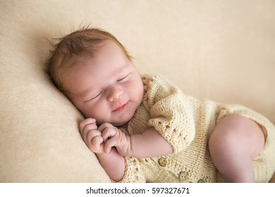 sweet newborn baby sleeps on a light blanket and smiling