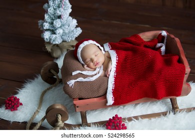 sweet newborn baby sleeps in a sled in Christmas costumes.