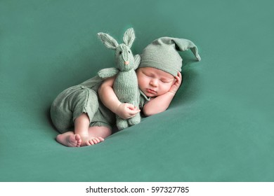 sweet newborn baby sleeps with a toy hare on a green background.