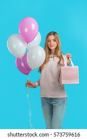 Sweet nice girl with baloons and little prersents bag in the hands on the blue background. Shopping mood. woman's happiness.