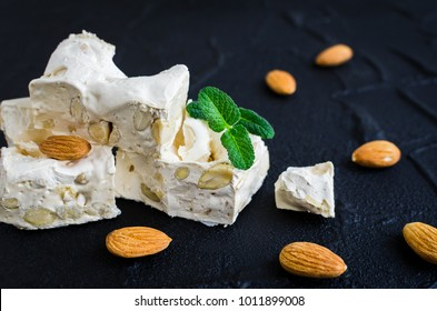 Sweet nougat with almonds on black stone background. Pieces of white nougat.