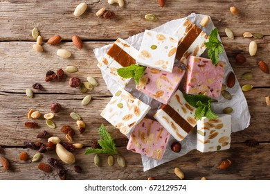 Sweet nougat with nuts, decorated with mint closeup on the table. horizontal view from above