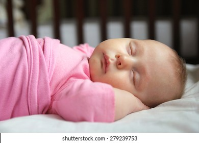A sweet one month old newborn baby girl is sleeping on her back in her crib, swaddled in a pink blanket.