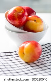 sweet, organic red and yellow plums in a white bowl, isolated on white background by the window with checkered table cloth, close up, vertical