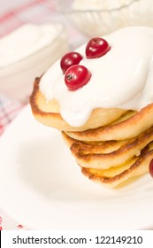 sweet pancakes with cranberries and sour cream closeup
