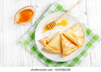Sweet pancakes with honey on a plate. The concept of food, breakfast,  pancake week.