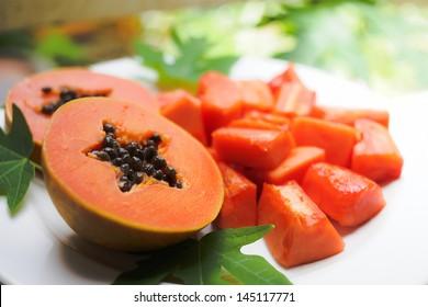 sweet papaya on the dish with green papaya leaf