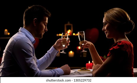 Sweet passionate couple on romantic date drinking champagne, Valentines day