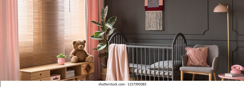 Sweet, pastel pink accessories in a classic, dark nursery bedroom interior with wooden furniture and a gray crib for a child